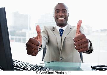 Entrepreneur working with a computer with the thumbs up in...