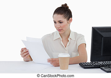 Focused businesswoman looking a document against a white...