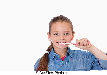 Healthy girl brushing her teeth against a white background