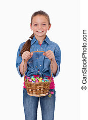 Portrait of a girl holding a basket full of Easter eggs