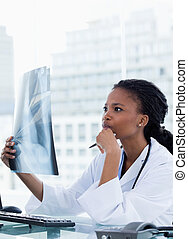 Portrait of a serious female doctor looking at a set of X-rays