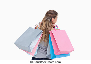 Back view of a woman holding shopping bags