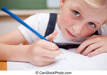 Close up of a serious schoolgirl writing something