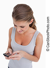 Portrait of a woman sending a text message against a white...