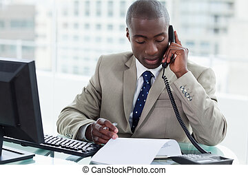 Entrepreneur making a phone call while reading a document in...