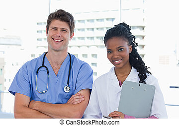 Happy doctors standing up in an office