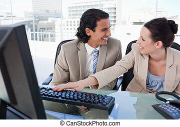 Laughing business team using a computer