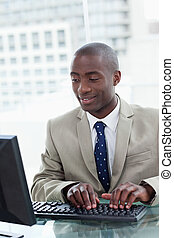 Portrait of a happy office worker using a computer in his...