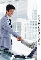 Portrait of an employee shaking the hand of his manager