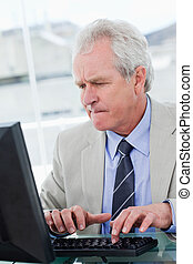 Portrait of a serious senior manager using a computer