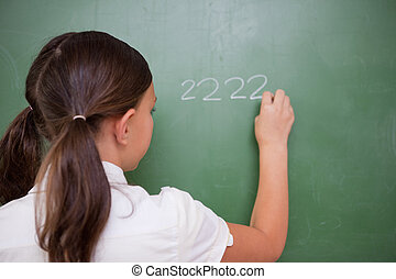 Girl writing numbers on a blackboard