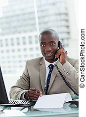 Portrait of a smiling entrepreneur making a phone call while...