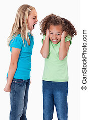 Portrait of an angry girl screaming at her friend against a...