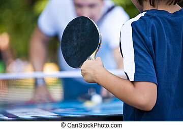 teenager plays Ping-Pong - teenager in a dark blue vest...