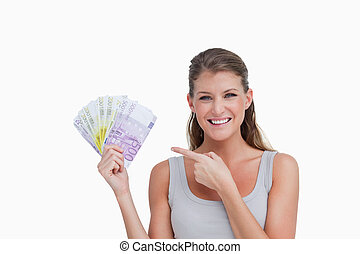 Woman pointing at bank notes against a white background