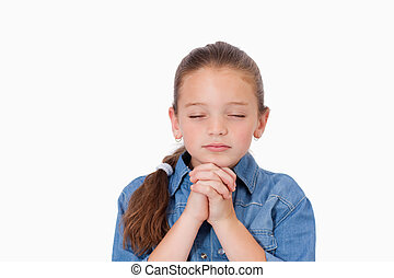 Little girl praying against a white background
