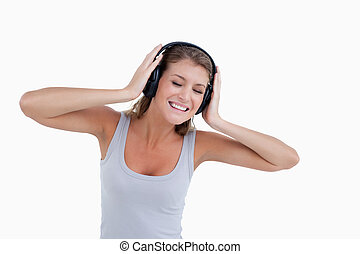 Happy woman dancing while listening to music against a white...