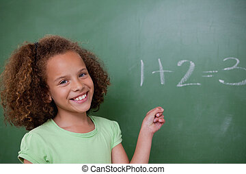 Cute schoolgirl pointing at an addition on a blackboard