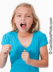 Portrait of a young girl screaming against a white...