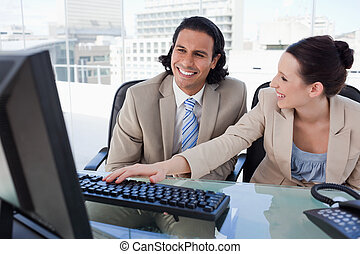 Happy business team using a computer
