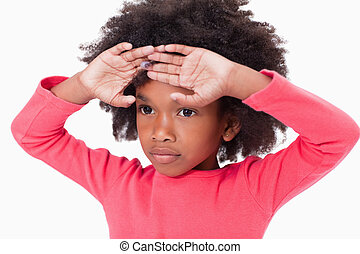 Cute girl with her hands on her forehead against a white...