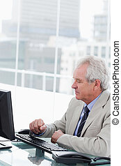 Portrait of a senior manager working with a computer