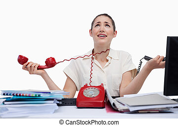 Stressed secretary answering the phones against a white...