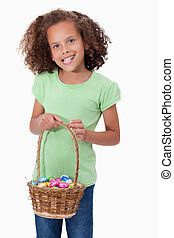 Portrait of a young girl holding a basket full of Easter...