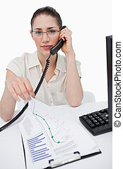 Portrait of a manager making a phone call while looking at statistics against a white background