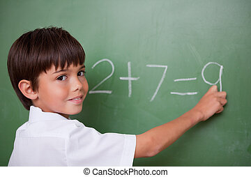 Happy schoolboy writing an addition on a chalkboard