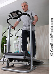 Middle-aged man jogging in gym