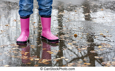 Boots in a puddle - Child standing in a puddle wearing a...