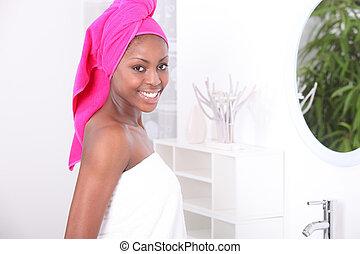 Woman stood in bathroom wearing towel