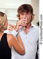 Young couple drinking champagne with their arms entwined