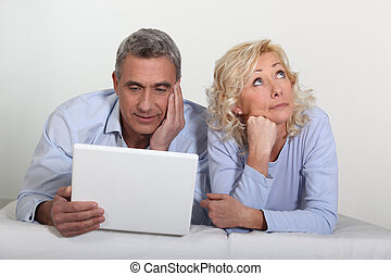 Middle aged couple with a laptop on their bed