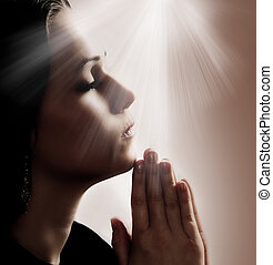 Woman Praying - Woman praying with lights shining down