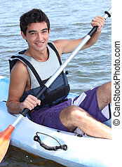 Young man paddling a kayak