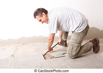 Manual worker disassembling old floor tiles - Happy manual...