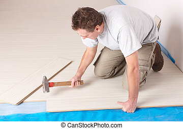 Worker installing a laminated flooring