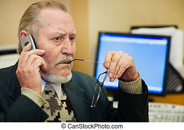 Senior at work place - Mature businessman talking on the...
