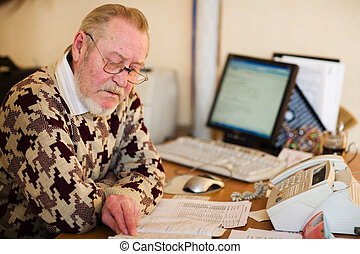 Senior at work place in office with computer notes and fax
