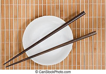 Asian Cuisine - Simple arrangment of chopsticks, mat and...