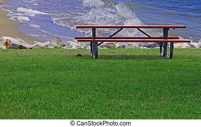 A Picnic table on a summer day along the rock lined shore of a beach with waves crasing in the background and room for your text.
