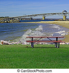 A Picnic table on a summer day along the rock lined shore of Yorktown Beach beach with the George P Coleman Bridge in the background and room for your text.