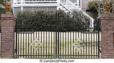 Black Iron Gate - Bricks and black iron gate in front of a...