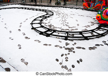 snow in the deserted lunapark - snow with footprints in the...