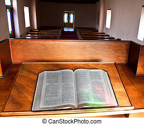 Empty church with lead glass doors with Bible lying open for...
