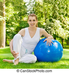 Happy fitness woman with pilates ball outdoors.