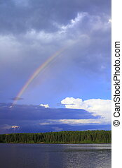 Rainbow over lake - Rainbow breaks through storm clouds...