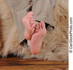 close-up of little boys bare feet crossed over